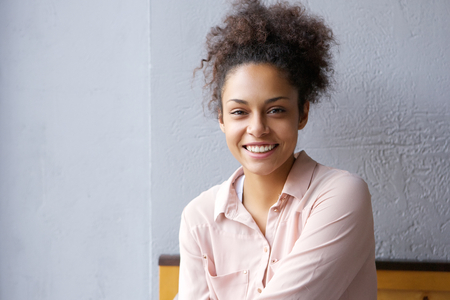 happy black woman: Close up portrait of a happy mixed race woman smiling indoors Stock Photo