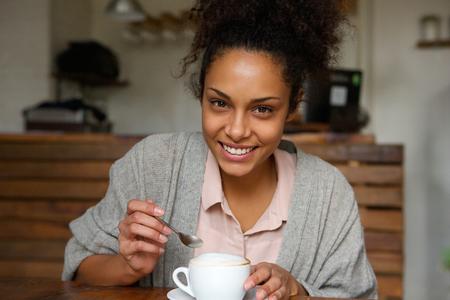 mujeres negras: Close up retrato de una mujer afroamericana joven feliz con la taza de café