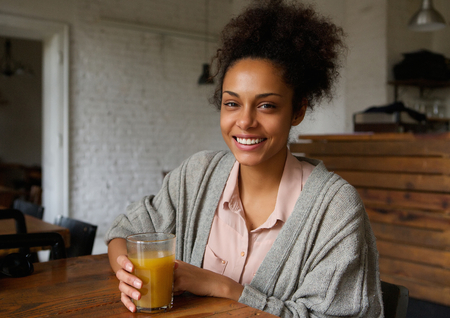 mixed race people: Portrait of an attractive smiling young woman with fruit juice drink