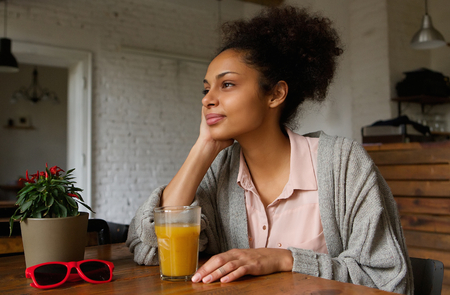 mixed race woman: Portrait of a beautiful african american woman sitting at home thinking Stock Photo