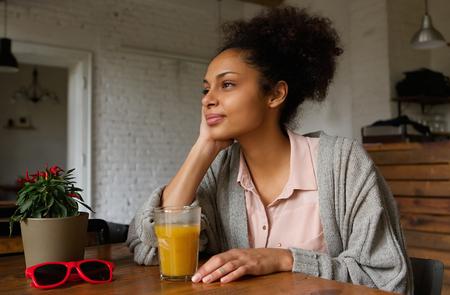 mujer pensando: Retrato de una hermosa mujer afroamericana sentado en casa pensando