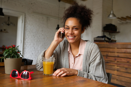 lady on phone: Portrait of a smiling young woman sitting at home and talking on mobile phone Stock Photo