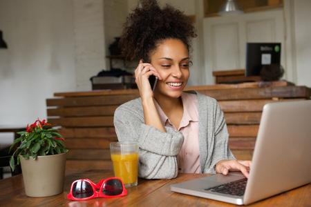 hablando por celular: Retrato de una mujer joven y sonriente con ordenador portátil y hablando por teléfono móvil Foto de archivo