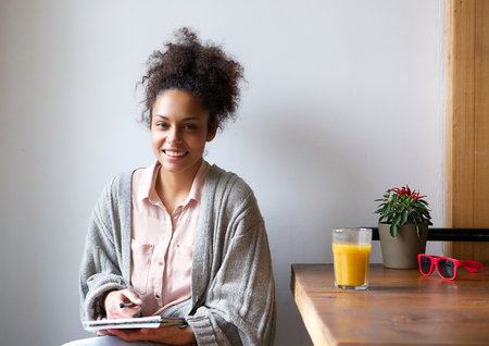 writing pad: Portrait of a smiling african american woman sitting at home with pen and paper Stock Photo