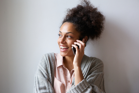 woman on phone: Close up portrait of a cheerful young woman talking on mobile phone