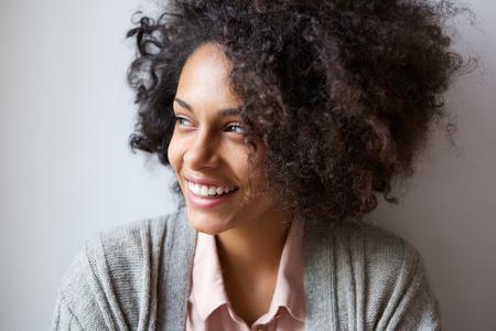 미소하고 멀리 찾고 아름 다운 검은 여자의 초상화를 닫습니다