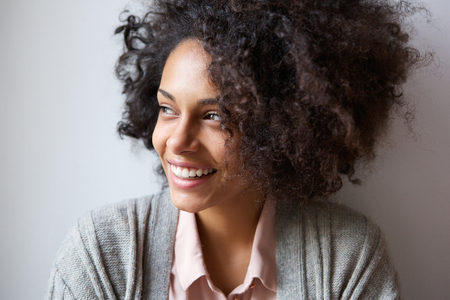black person: Close up portrait of a beautiful black woman smiling and looking away Stock Photo