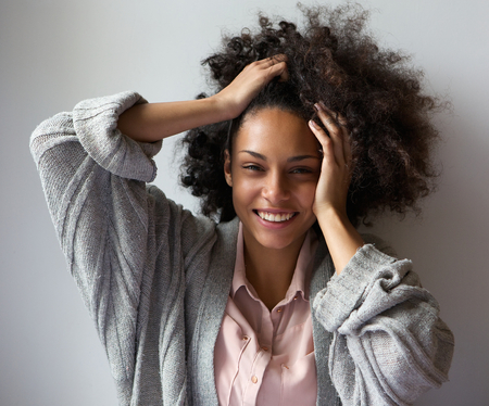 Close up portrait of a cheerful young attractive black woman smiling with hands in hair