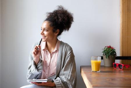 펜과 종이로 집에 앉아 행복 한 젊은 여자의 초상화 스톡 콘텐츠