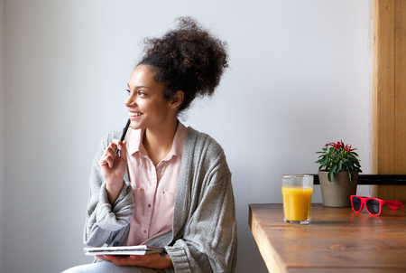 Portrait of a happy young woman sitting at home with pen and paper