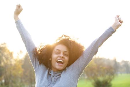 Porträt einer fröhlichen jungen schwarzen Frau lächelnd mit erhobenen Armen