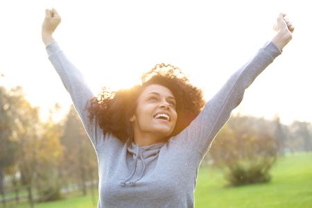 manos levantadas: Retrato de una mujer joven alegre y sonriente con los brazos levantados Foto de archivo