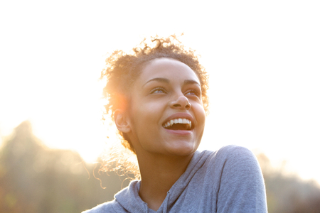 looking up: Portrait of an attractive young woman laughing and looking up