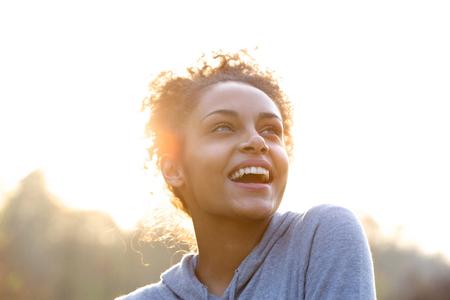Portret van een aantrekkelijke jonge vrouw lachen en kijken omhoog Stockfoto