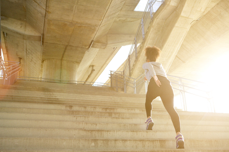 workout: Young exercise woman running alone up stairs