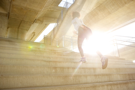 Portrait of a young woman running up stairs in the city