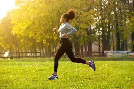 fit woman: Side view portrait of a young woman running outdoors Stock Photo
