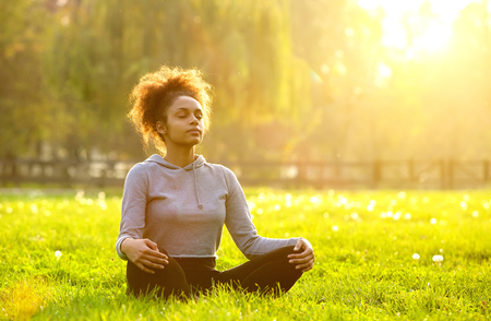 calmness: Young african american woman meditating in nature Stock Photo