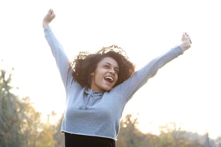 Portret van een zorgeloze jonge vrouw lachend met opgeheven armen