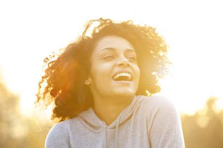 natural looking: Close up portrait of a happy african american girl laughing outdoors Stock Photo