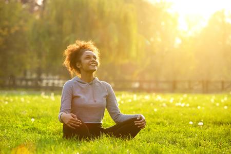 Gelukkige jonge vrouw zit buiten in yoga-positie Stockfoto