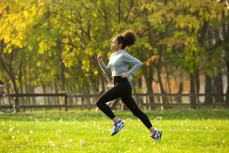 Side view full body portrait of a young woman jogging outdoors