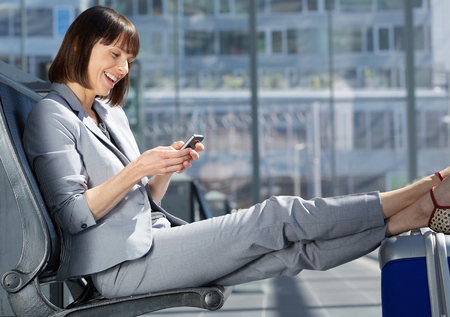 business bag: Side portrait of a traveling business woman smiling with mobile phone