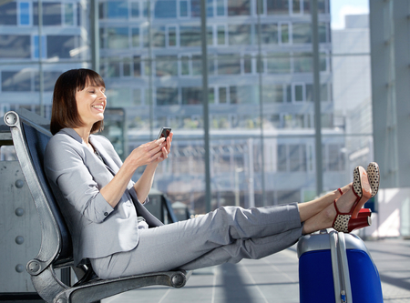 return trip: Side portrait of a happy business woman sitting with feet on bag and looking at mobile phone