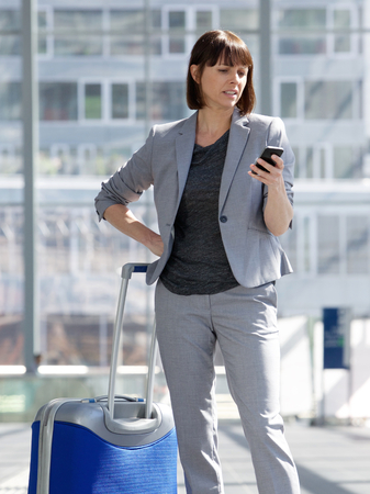 return trip: Portrait of a traveling business woman looking at mobile phone