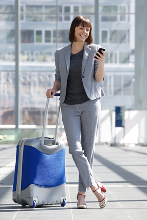 return trip: Full body portrait of a smiling business woman standing with mobile phone and bag at airport