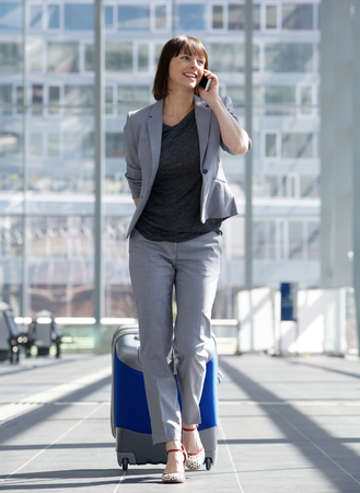 return trip: Full length portrait of a smiling business woman talking on mobile phone at airport