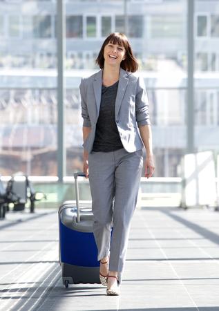 空港でスーツケースを持って歩く幸せなビジネス女性の全身肖像画