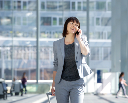 woman business suit: Portrait of a smiling business woman walking and talking with mobile phone at airport Stock Photo