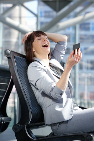 mobile business: Portrait of a happy business woman reading text message on mobile phone Stock Photo