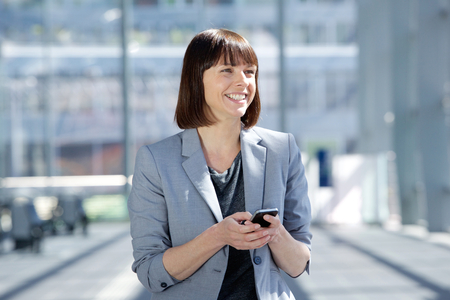 middle aged woman smiling: Close up portrait of a smiling business woman walking with cell phone Stock Photo