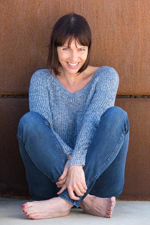 Ritratto di una donna spensierata seduto e sorridente Archivio Fotografico - 41083179
