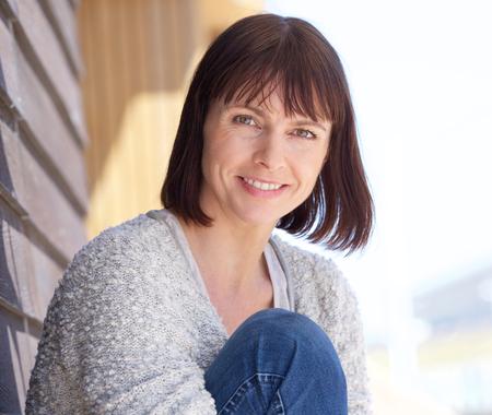 Close-up portret van een rijpe vrouw glimlachend buitenshuis