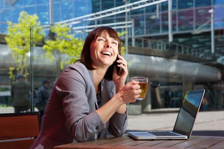 work break: Portrait of a happy business woman talking on mobile while on break from work