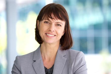 Feche acima do retrato de uma mulher de negócios, sorrindo ao ar livre profissional