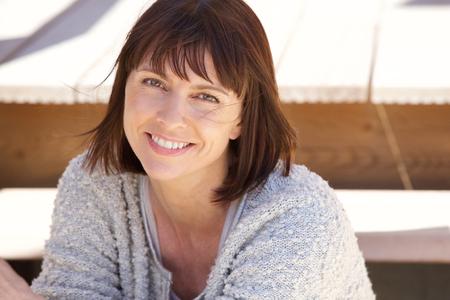 femme brune: Close up portrait d'une femme plus �g�e saine sourire � l'ext�rieur