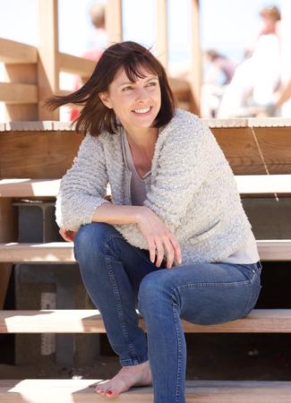 mujer alegre: Retrato de una mujer alegre que se sienta al aire libre en los pasos