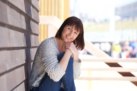행복 한 중간 나이 든 여자의 초상화 밖에 서 앉아