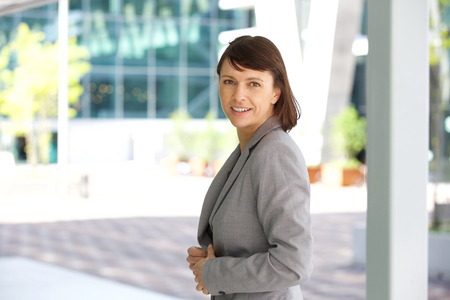 executive woman: Close up portrait of an older business woman smiling outdoors