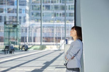 persona pensando: Retrato lateral de una mujer de negocios feliz de pie por sí sola