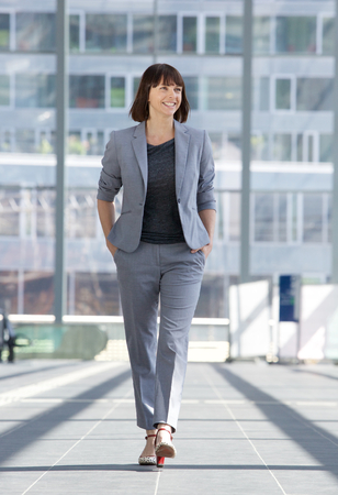 full suit: Full length portrait of a relaxed business woman smiling and walking