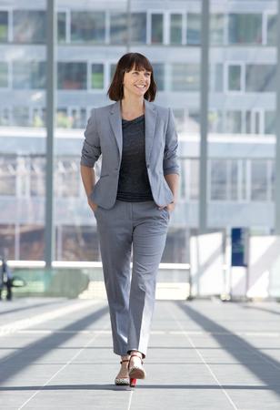 completos: Retrato de cuerpo entero de una mujer de negocios relajado sonriente y caminando