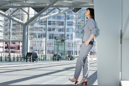 Full body side portrait of a business woman standing inside city building