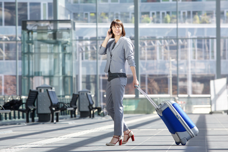 cuerpo entero: Retrato del lado del cuerpo de una mujer de negocios sonriente caminando con bolsa y el teléfono móvil