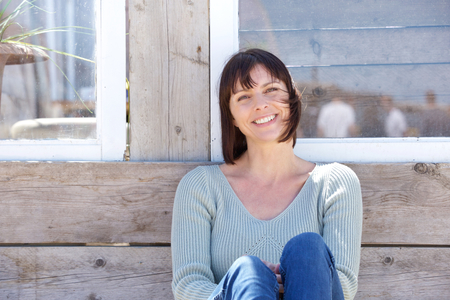 middle adult: Close up portrait of a happy middle aged woman smiling outdoors