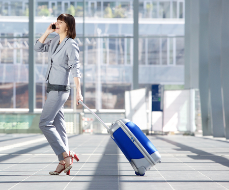 행복한 비즈니스 여자의 전체 길이 측면 초상화 가방 걷고 공항에서 휴대 전화에 얘기